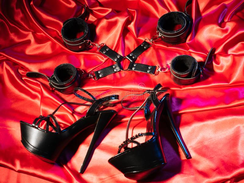 Top view of bdsm outfit. Bondage and a pair of black high-heeled shoes on the red linen. Adult sex games. Kinky lifestyle stock images