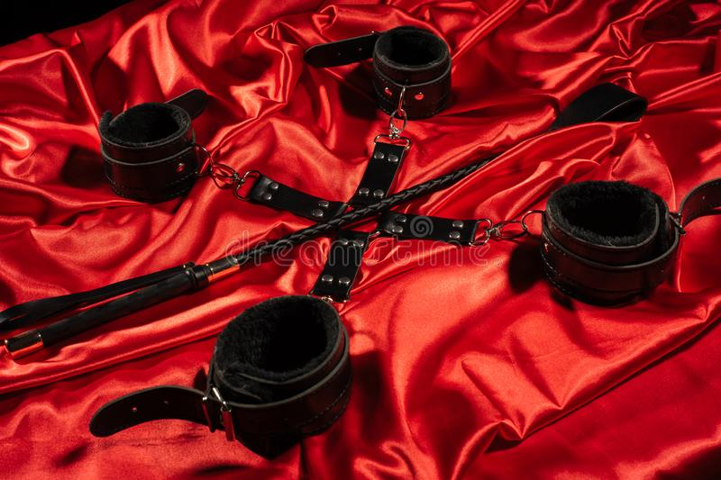 Top view of bdsm outfit. Bondage and spank on the red linen. Adult sex games. Kinky lifestyle stock photos