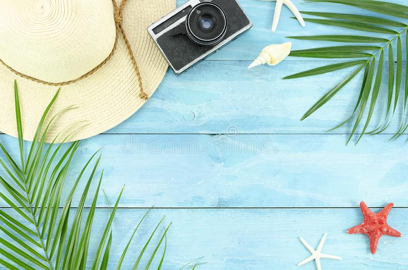 Top view beach accessories flyer, palm leaf branches and wicker hat on blue planks frame. Summer flat lay background.  royalty free stock photo