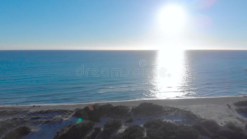 Top view of beach with blue sea and sun on horizon. Art. People on beach relax enjoying blue horizon of touching sea and royalty free stock images