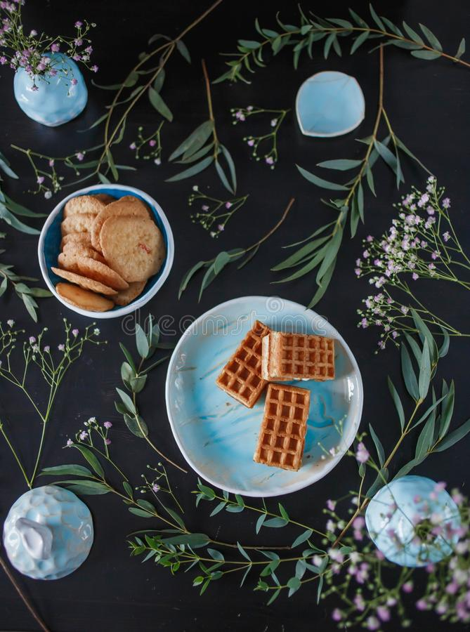 Top view beautiful blue handmade tableware and sweet baking ginger cookies, waffles. On a black wooden background with green leaves and pink flowers. Top view royalty free stock photo