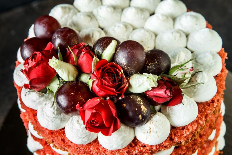 Top view of beautiful cake with bizet, grapes and roses. Top view of beautiful multi-layer cake with white bizet, grapes and red and white roses stock images