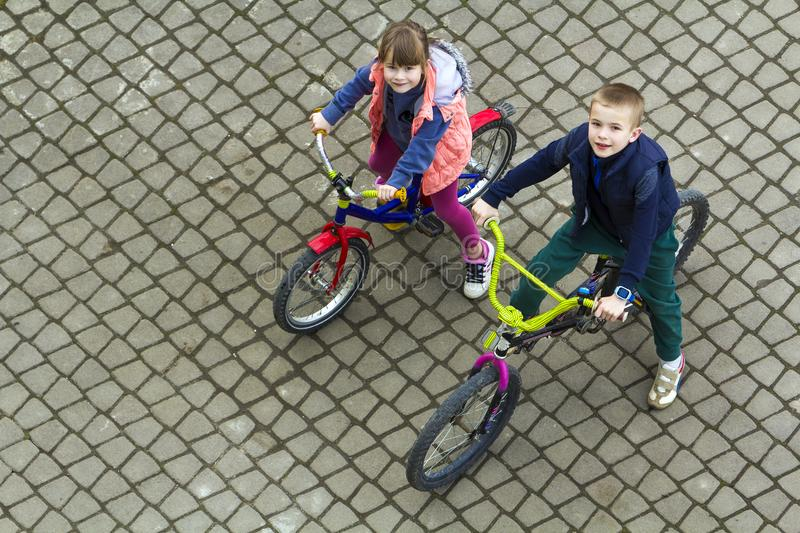 Top view of beautiful children brother and sister riding bicycles on cool spring day looking upward. Outdoors activities.healthy l stock image