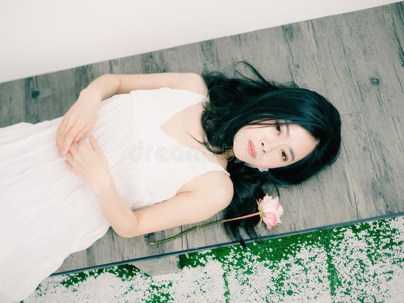 Top view of a beautiful Chinese girl laying down on floor with c royalty free stock image