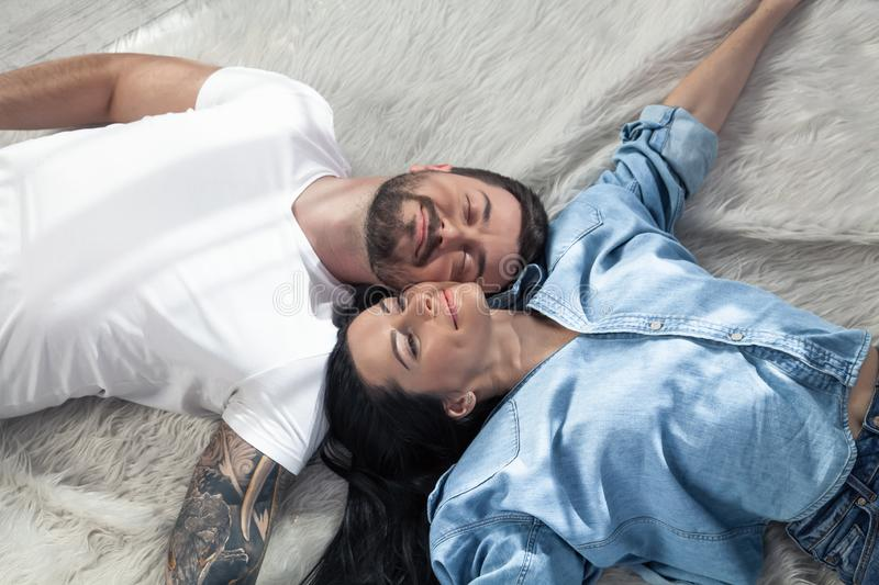 Top view of a beautiful couple laying over white background. girl with long dark hair. they are in love stock photography
