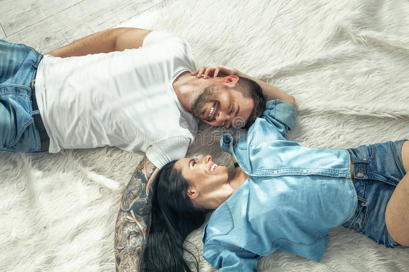 Top view of a beautiful couple laying over white background. girl with long dark hair. they are in love stock photo