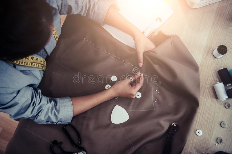 Top view of beautiful dressmaker sewing dress fabric with hand. Fashion designer tailor or sewer in workshop studio designing new. Collection clothes. Business stock photography
