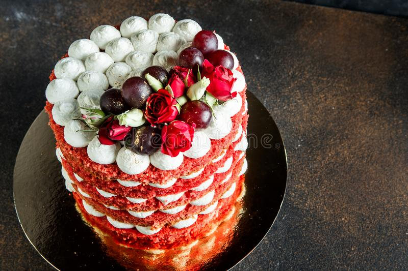 Top view of beautiful cake with bizet, grapes and roses. Top view of beautiful multi-layer cake with white airy bizet, red grapes and red and white roses royalty free stock photos