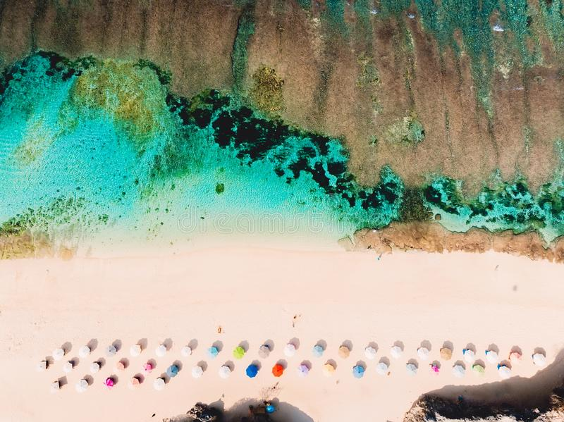 Top view of beautiful sand beach with turquoise ocean water and colorful umbrellas, aerial drone shot royalty free stock photography