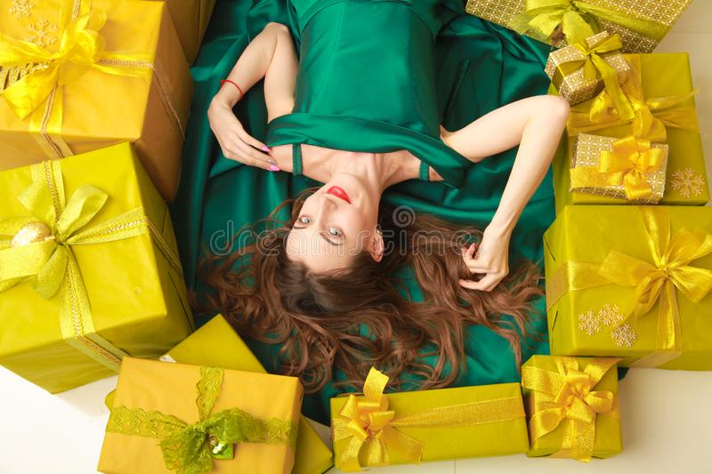 Top view of beautiful slender fashion woman in trendy green dress lying with golden boxes with gifts. cheerful girl stock images