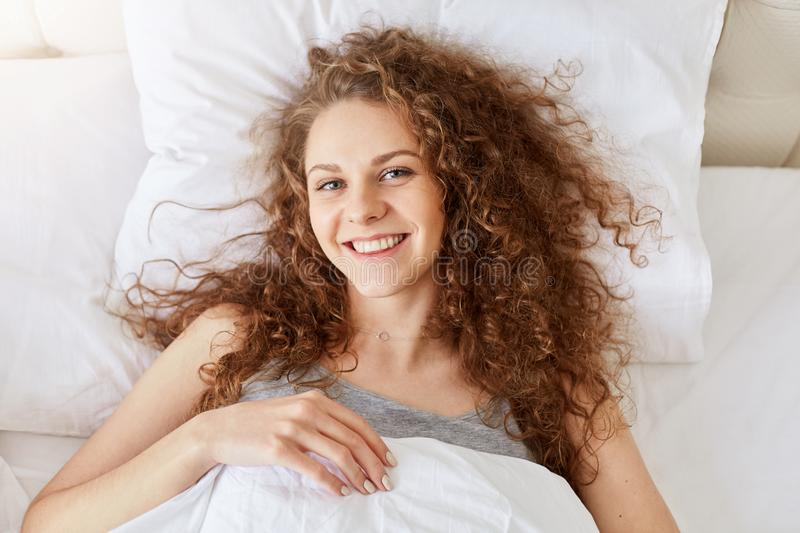 Top view of beautiful smiling curly female feels relaxed and happy in morning after awakening, lies on white pillow, rejoices day royalty free stock photo