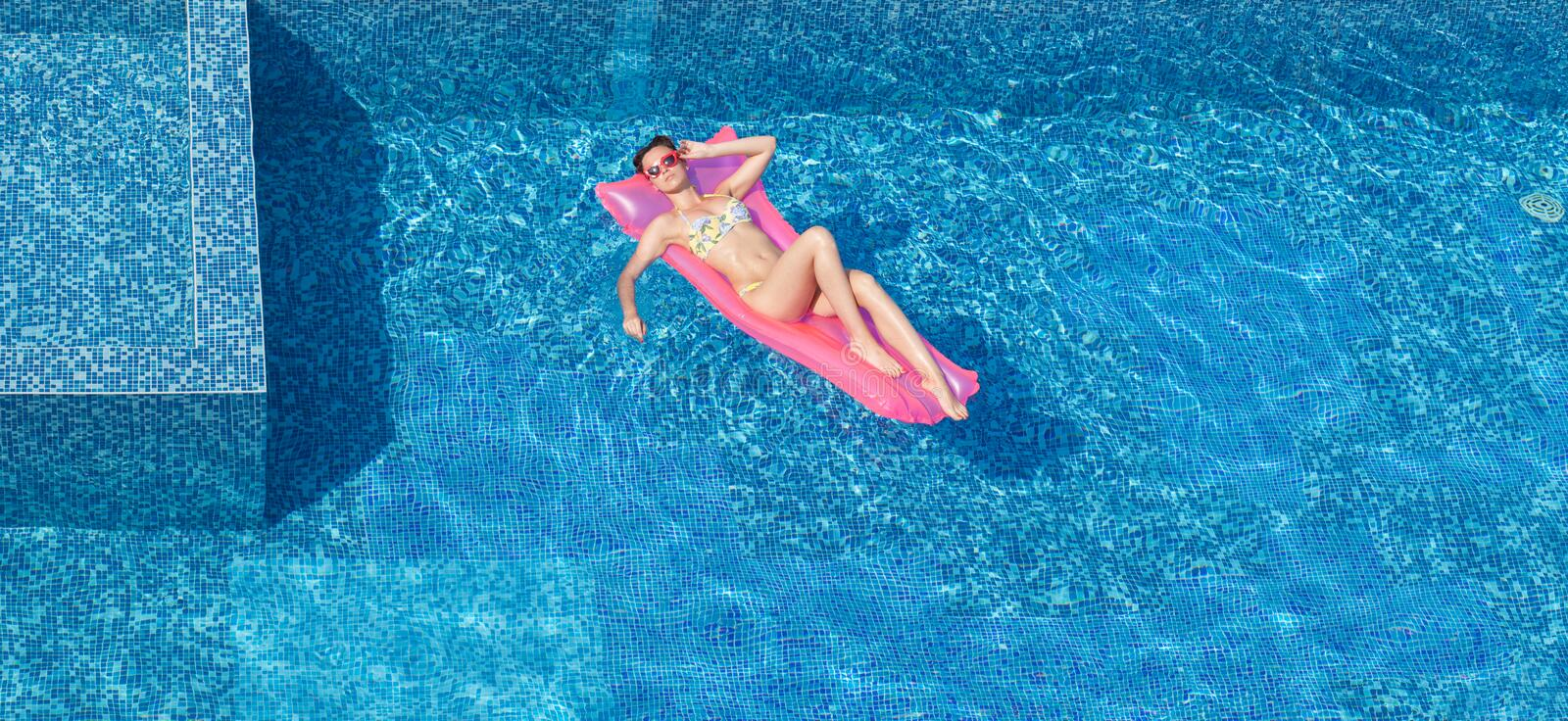 Top view of beautiful tanning woman in pool stock image