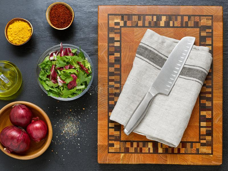 Top view of a beautiful wooden cutting board with a knife. On a dark background with salad, onions, spices and butter. The concept of vegetarian food royalty free stock image