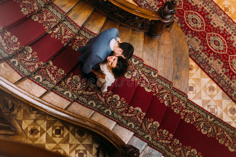 Top view on beautiful young bride and handsome groom kissing at old stairs with the background of gorgeous wooden. Vintage interior royalty free stock photography