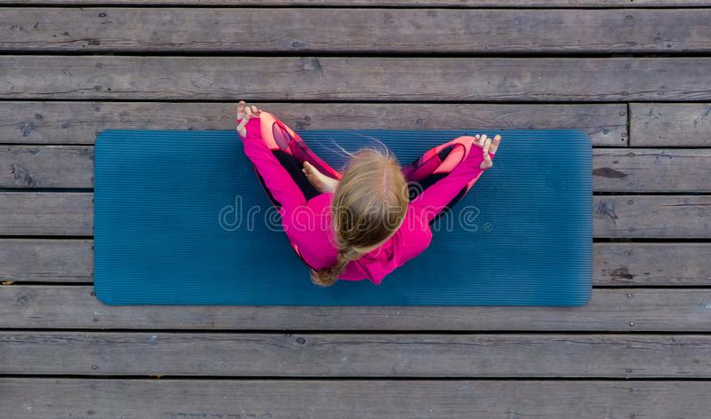 Top view of beautiful young fitness woman working out on wooden floor terrace, doing yoga exercise, full length. Top view of beautiful young fitness woman royalty free stock photo