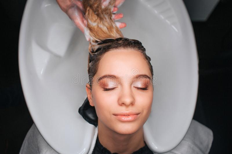 Top view of beautiful young woman with closed eyes smiling while hairdresser washing blonde hair. Hair care in salon royalty free stock images