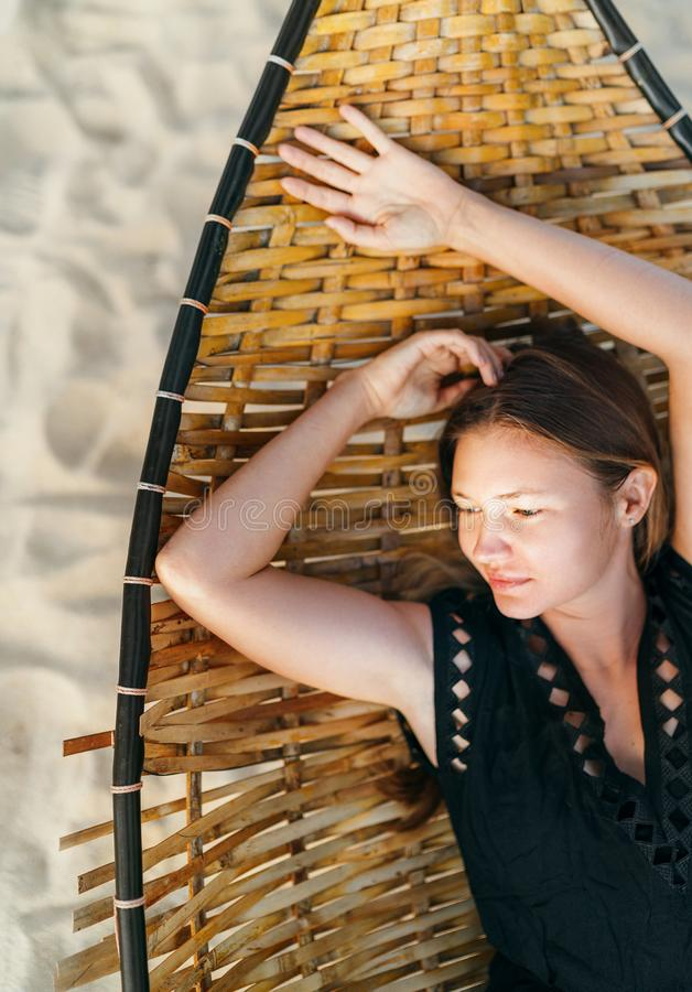 Top view of beautiful young woman lying in hammock on the sandy beach, looking to a sunrise and thinking royalty free stock image