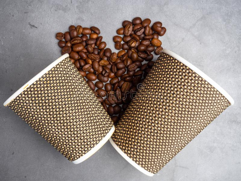 Top view big and small paper coffee to go cups and heart made from coffee beans, mock up paper cups, copy space. Top view paper coffee to go cups and heart made royalty free stock photo