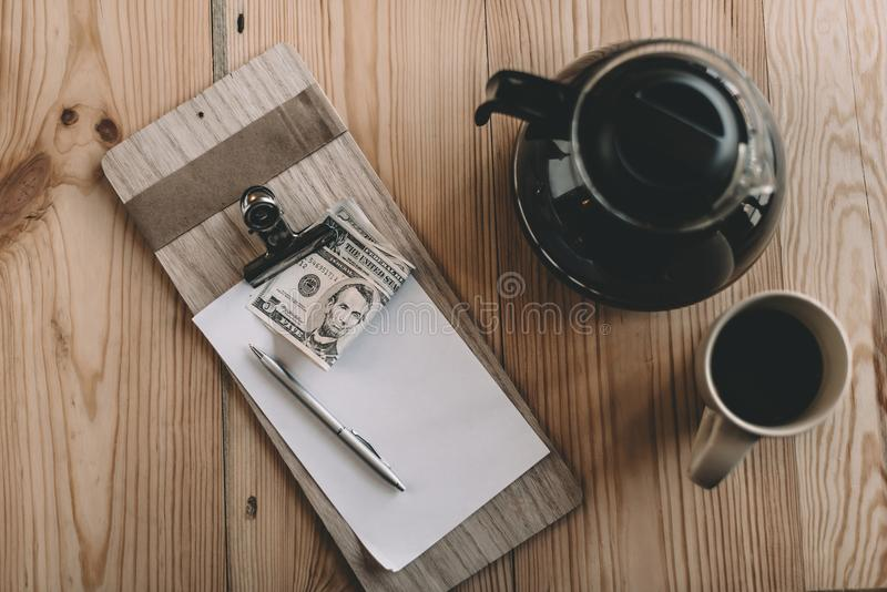 top view of bill, cash payment, glass kettle and cup of coffee on tabletop in cafe stock photo