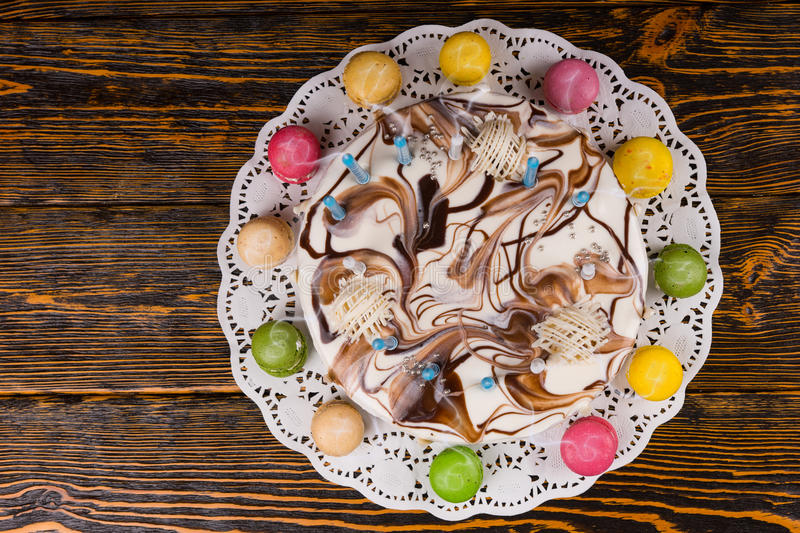 Top view of birthday cake with lots of candles near different co. Lored macarons, on wooden desk royalty free stock photography