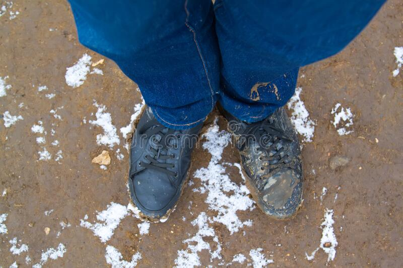 Top view of black boots and legs in blue jeans all covered in mud standing on dirty ground covered with snow. Concept of leaving. The comfort zone to meet new stock photography
