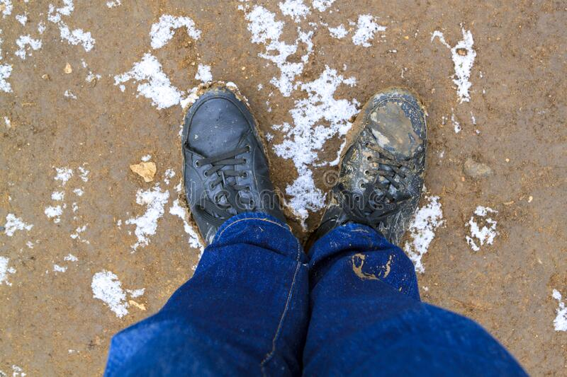 Top view of black boots and legs in blue jeans all covered in mud standing on dirty ground covered with snow. Concept of leaving. The comfort zone to meet new stock images