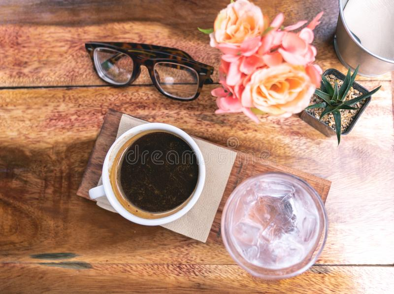 Top view black coffee in white ceramic cup on wooden background. With flower and retro glasses royalty free stock image
