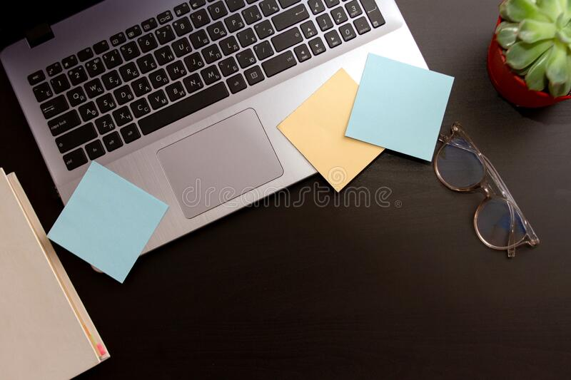 Top view black desktop with silver laptop computer, stickers and glasses. Flat lay. Mockup with copyspace stock image