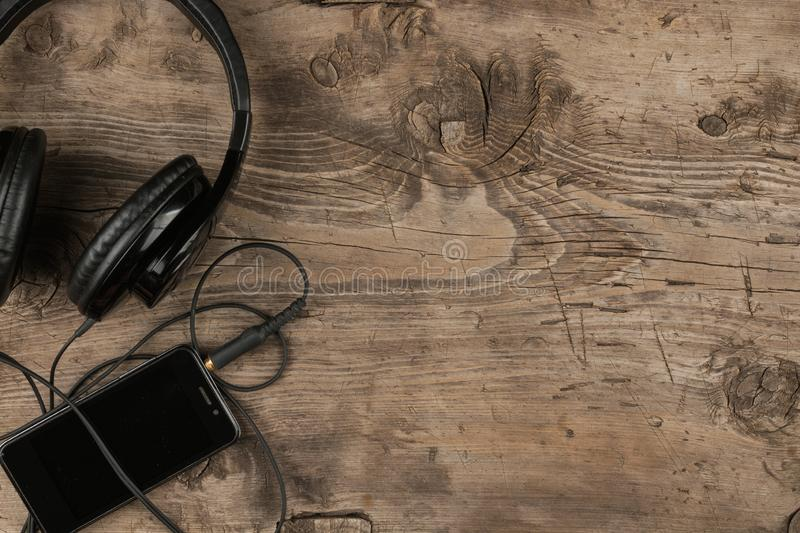 Top view. Black headphone and mobile phone on old wooden desk, vintage background royalty free stock photography