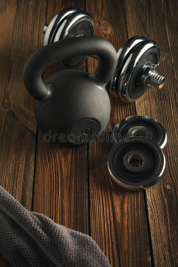 Top view of black iron kettlebell, dumbbell and grey towel on wooden floor Sport background with copyspace royalty free stock images