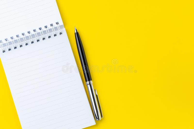 Top view of black pen with clean white notebook open with copy space on solid yellow table background for presentation, writer or. School education, blogger royalty free stock photo