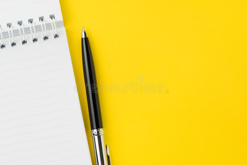 Top view of black pen with clean white notebook open with copy space on solid yellow table background for presentation, writer or stock photography