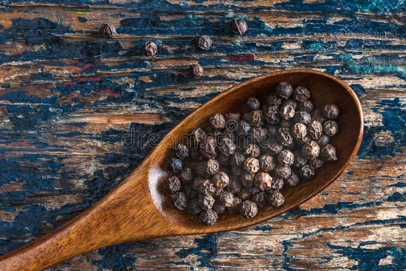 Black Peppercorns on a Wood Spoon stock photography