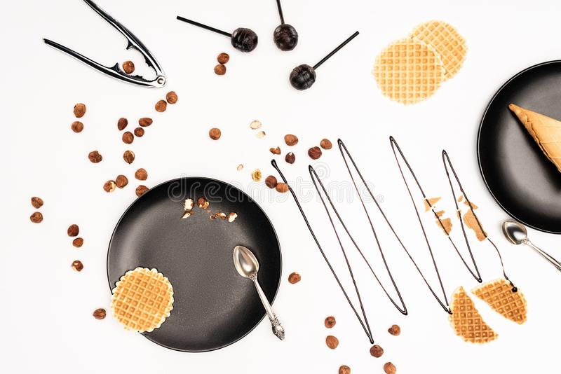 top view of black plates with scattered hazelnuts royalty free stock photo