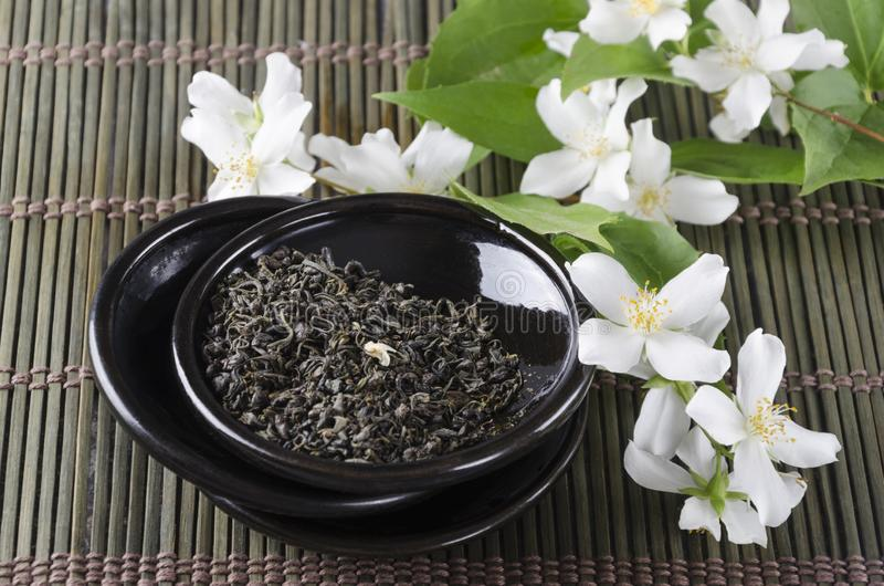 Closeup of dry green tea and jasmine flowers on the black saucer, green bamboo serving mat royalty free stock photography