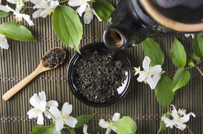 Top view of black teapot and saucer full of dry green tea, wooden spoon and aromatic fresh jasmine flowers on the green wicker mat stock photo