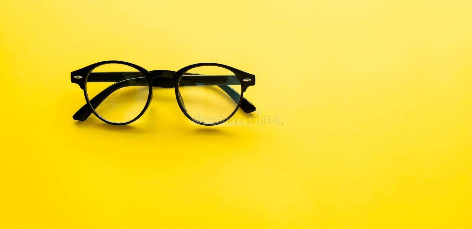 Top view. Black vintage glasses of accessory fashion, minimal Style on yellow background use for wallpaper and screen royalty free stock photography