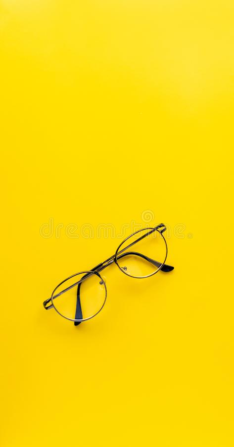 Top view. Black vintage glasses of accessory fashion, minimal Style on yellow background use for wallpaper and screen royalty free stock photo
