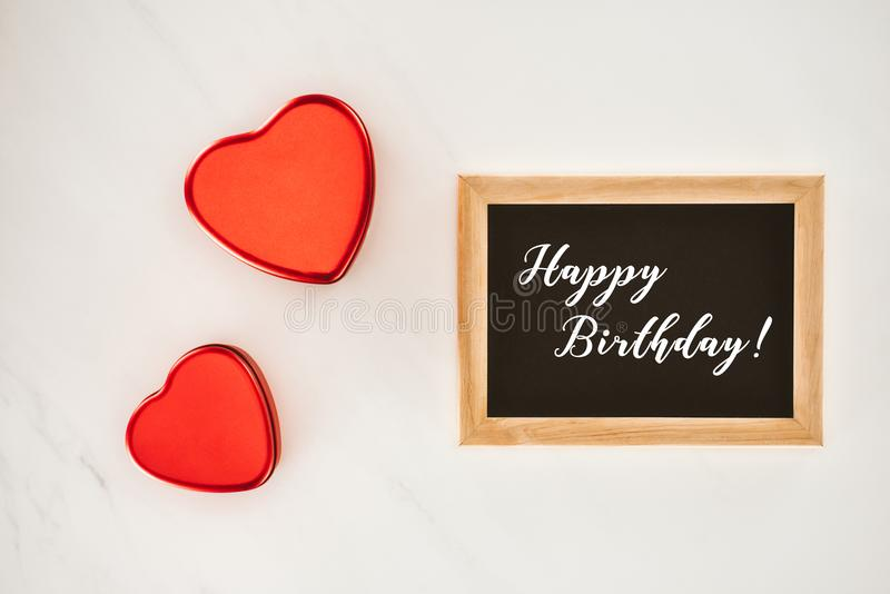 top view of blackboard in frame with HAPPY BIRTHDAY lettering with heart shaped stock image