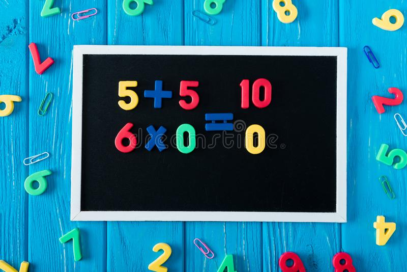 top view of blackboard with math sums colorful numbers and paper clips on blue wooden stock photo