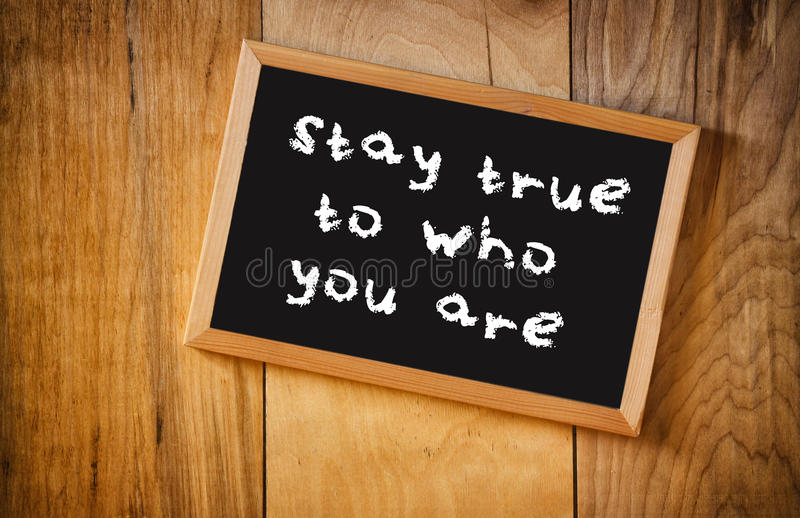 Top view of blackboard with the phrase stay true to who you are, over wooden background royalty free stock image