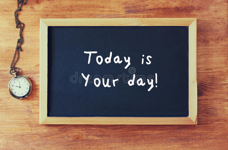 Top view of blackboard with the phrase today is your day written on it next to old clock over wooden table stock images
