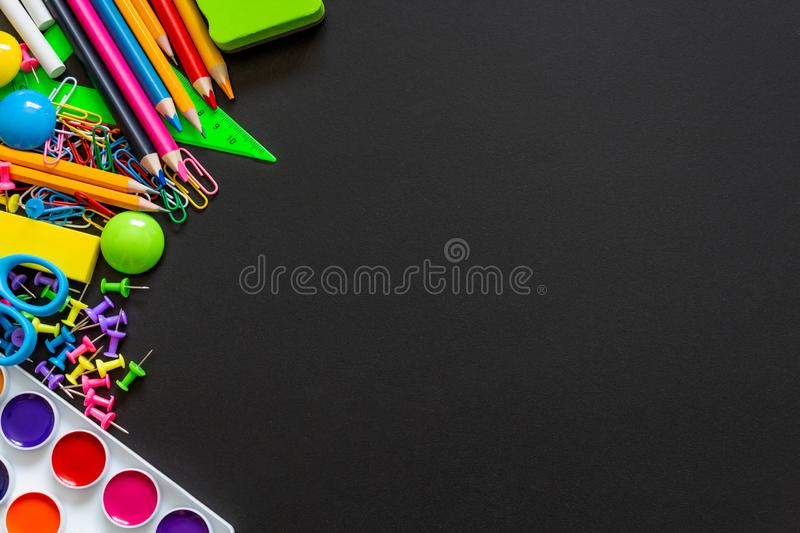 Colourful school supplies on black chalkboard background. stock photo
