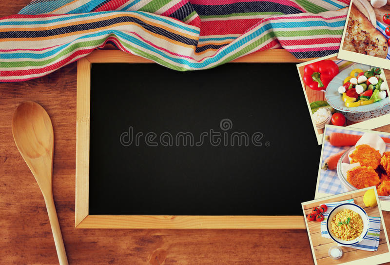 Top view of blackboard and wooden spoon over wooden table and collage of photos with various food and dishes royalty free stock images