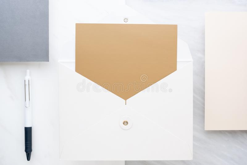 Top view of  blank golden card in white envelop on two layer step of marble table top.Mock up template for display of design. Modern business items royalty free stock images
