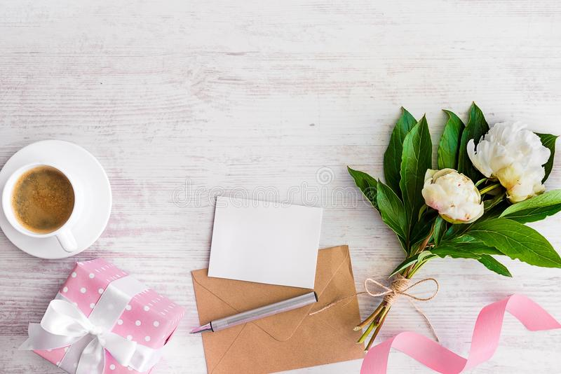 Top view of blank note, kraft envelope, coffee cup and peony flowers over white wood rustic background.Copy space. stock photos