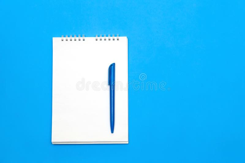 Top view of blank note paper with pen on blue wood table for background. stock photography