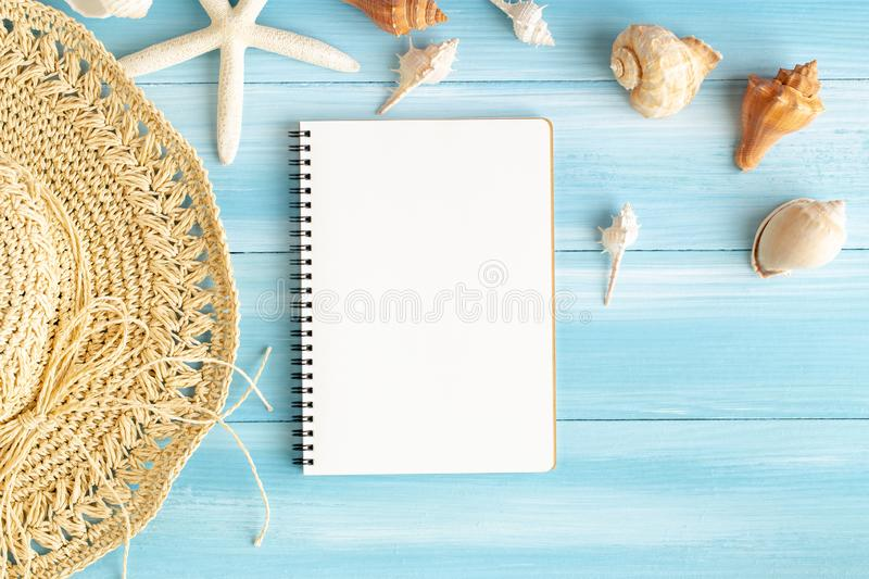 Top view of blank notebook on blue wood table, sea shells and starfish on a blue wooden background, Summer concept stock image