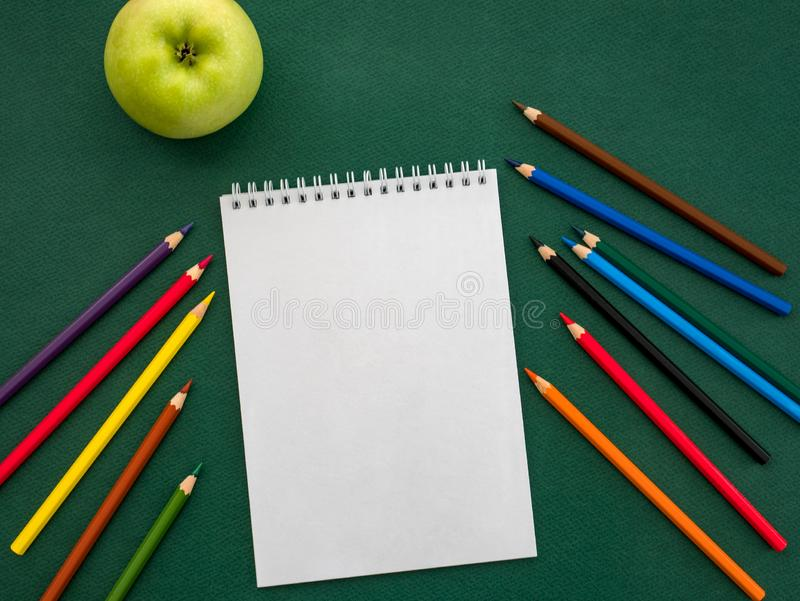 Top view of blank notebook, coloured pencils and green apple. Ba. Ck to school concept royalty free stock photo
