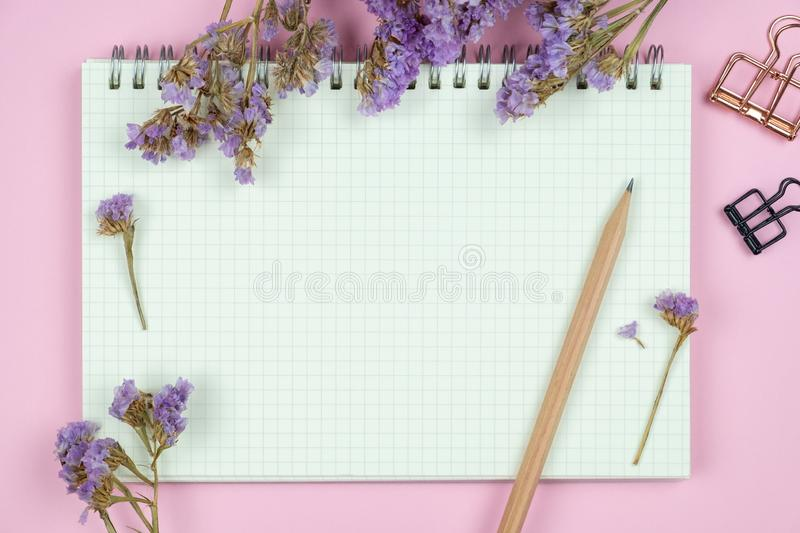 Top view of blank notebook and flower on pink background royalty free stock images